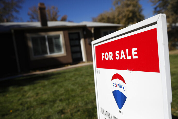 FILE - In this Oct. 22, 2019 file photo, a sign stands outside a home for sale in southeast Denver.   U.S. mortgage rates turned down this week, lowering the cost of purchasing a home and supporting the housing market. Mortgage giant Freddie Mac said Thursday, Nov. 21,  that the average rate for a 30-year fixed mortgage fell to 3.66% this week from 3.75% last week. The average 15-year rate declined to 3.15% from 3.2%.(AP Photo/David Zalubowski, File)
