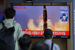 """People watch a TV screen showing a news program reporting about North Korea's missiles with file image in Seoul, South Korea, Wednesday, Sept. 15, 2021. North Korea fired two ballistic missiles into waters off its eastern coast Wednesday afternoon, two days after claiming to have tested a newly developed missile in a resumption of its weapons displays after a six-month lull. The letters read """"North Korea fired two ballistic missiles."""" (AP Photo/Lee Jin-man)"""