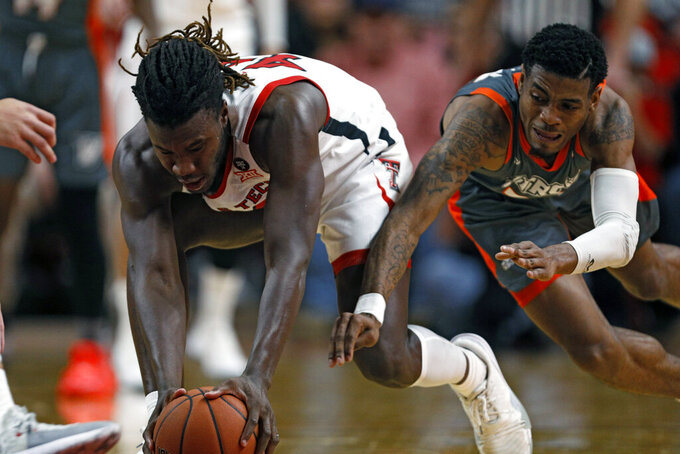 Texas Tech's Chris Clarke (44) and Texas-Rio Grande Valley's Jordan Jackson (22) dive for the ball during the second half of an NCAA college basketball game Saturday, Dec. 21, 2019, in Lubbock, Texas. (AP Photo/Brad Tollefson)