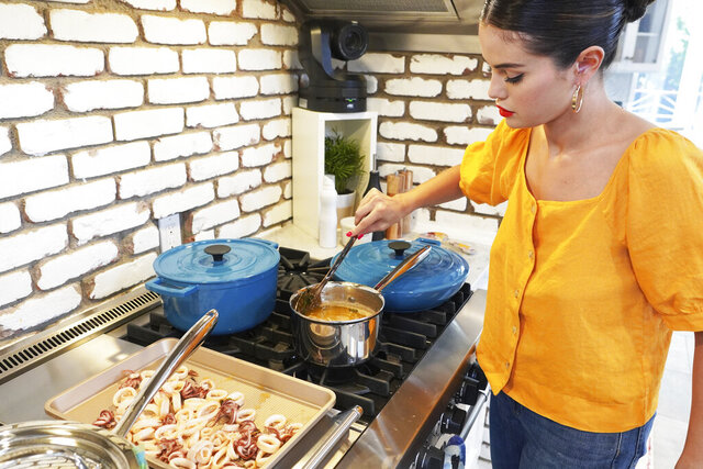 """This image released by HBO Max shows Selena Gomez from """"Selena + Chef,"""" a 10-episode cooking series that debuts Thursday on the HBO Max streaming service. (HBO Max via AP)"""