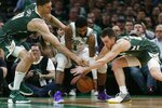 Milwaukee Bucks' Brook Lopez (11) and Pat Connaughton, right, and Boston Celtics' Kyrie Irving (11) reach for the ball during the first half of Game 3 of a second-round NBA basketball playoff series in Boston, Friday, May 3, 2019. (AP Photo/Michael Dwyer)