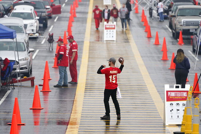 A fan throws a football outside Arrowhead Stadium before an NFL football game between the Kansas City Chiefs and the Houston Texans Thursday, Sept. 10, 2020, in Kansas City, Mo. (AP Photo/Charlie Riedel)