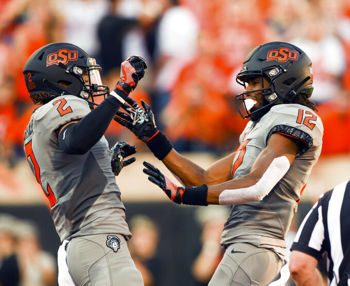 Oklahoma State wider receiver Tylan Wallace, left, celebrates with fellow wide receiver Jordan McCray after scoring a touchdown during the first half of an NCAA college football game against McNeese in Stillwater, Okla., Saturday, Sept. 7, 2019. (AP Photo/Brody Schmidt)