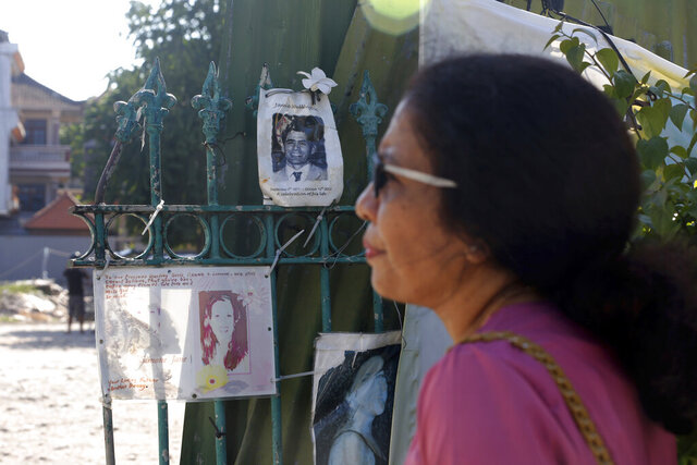 Ni Luh Erniati stands outside the site of the Sari Club bombing, with photographs of victims displayed on a gate in Bali, Indonesia on Friday, April 26, 2019. Erniati's husband, Gede Badrawan, was one of 202 people killed in the 2002 bombings, which targeted the Sari Club and nearby Paddy's Pub. It took months before officials were able to identify Gede's remains. (AP Photo/Firdia Lisnawati)