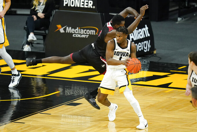 Iowa guard Joe Toussaint (1) grabs a rebound in front of Northern Illinois forward Chris Johnson, left, during the first half of an NCAA college basketball game, Sunday, Dec. 13, 2020, in Iowa City, Iowa. (AP Photo/Charlie Neibergall)