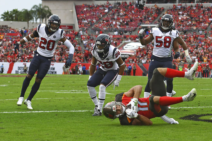 Tampa Bay Buccaneers wide receiver Justin Watson (17) scores on a 8-yard touchdown reception after getting by Houston Texans strong safety Justin Reid (20), cornerback Vernon Hargreaves III (28) and linebacker Peter Kalambayi (58) during the first half of an NFL football game Saturday, Dec. 21, 2019, in Tampa, Fla. (AP Photo/Jason Behnken)