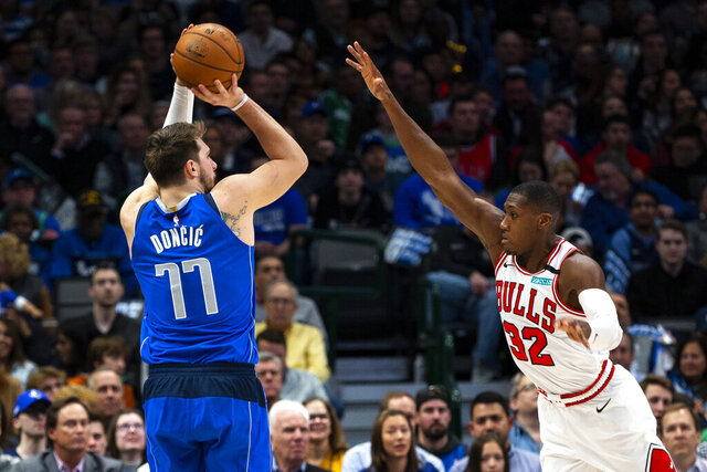 Dallas Mavericks forward Luka Doncic (77) attempts to shoot as Chicago Bulls guard Kris Dunn (32) defends during the first half of an NBA basketball game, Monday, Jan. 6, 2020, in Dallas. (AP Photo/Sam Hodde)