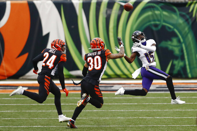 Baltimore Ravens wide receiver Marquise Brown (15) can't make the catch on a pass as Cincinnati Bengals free safety Jessie Bates (30) and strong safety Vonn Bell (24) defend during the first half of an NFL football game, Sunday, Jan. 3, 2021, in Cincinnati. (AP Photo/Aaron Doster)