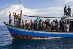 Ethnic Rohingya people react at a rescue ship from the deck of a boat off North Aceh, Indonesia, Wednesday, June 24, 2020. Indonesian fishermen discovered dozens of hungry, weak Rohingya Muslims on the wooden boat adrift off Indonesia's northernmost province of Aceh, an official said. (AP Photo/Zik Maulana)