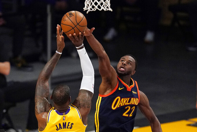 Los Angeles Lakers forward LeBron James, left, has his shot blocked by Golden State Warriors forward Andrew Wiggins during the first half of an NBA basketball Western Conference Play-In game Wednesday, May 19, 2021, in Los Angeles. (AP Photo/Mark J. Terrill)