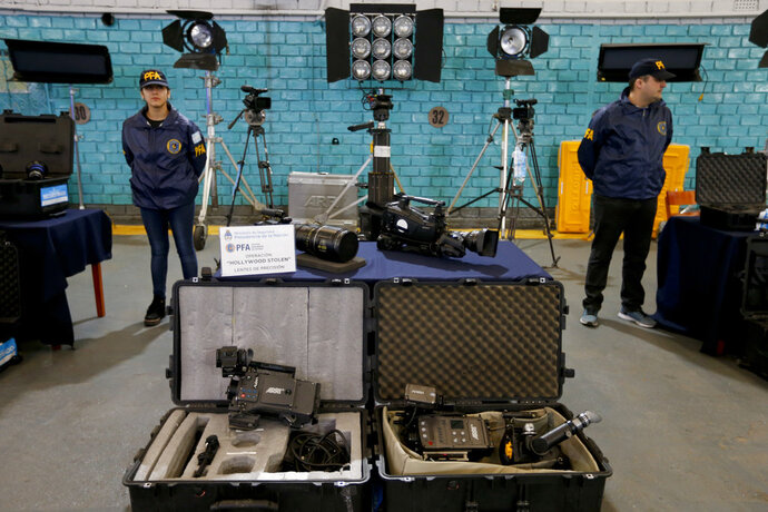 Police next to stolen film equipment during a media presentation at the police department in Buenos Aires, Argentina, Friday, Sept. 14, 2018. Argentine authorities say they have seized about $3 million in cameras, lenses and other film equipment stolen in Hollywood and New York. (AP Photo/Natacha Pisarenko)