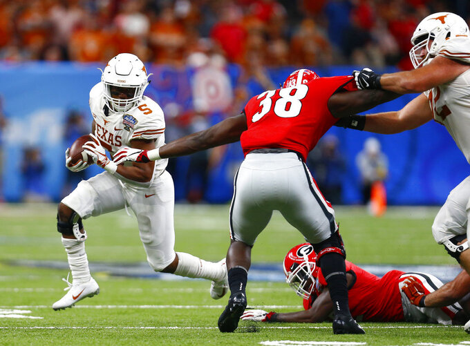 Texas running back Tre Watson (5) carries against Georgia linebacker Azeez Ojulari (38) during the first half of the Sugar Bowl NCAA college football game in New Orleans, Tuesday, Jan. 1, 2019. (AP Photo/Butch Dill)