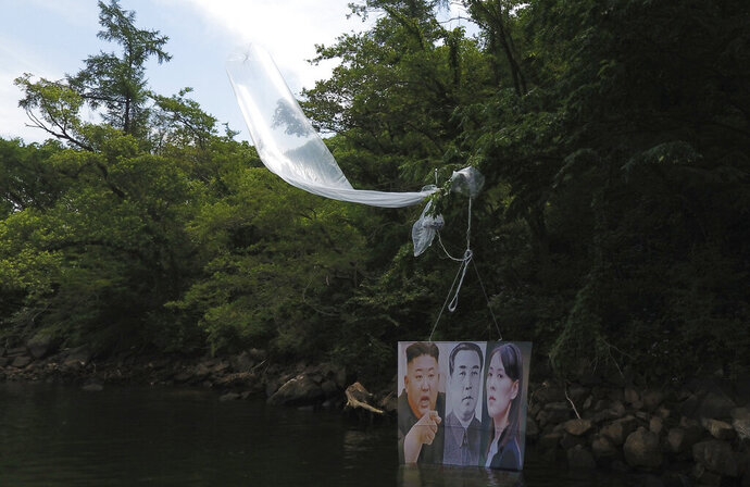 A balloon carrying a banner with images of North Korean leader Kim Jong Un, left, the late leader Kim Il Sung, center, and Kim Yo Jong, the powerful sister of Kim Jong Un, released by Fighters For Free North Korea, is seen in Hongcheon, South Korea, Tuesday, June 23, 2020. A South Korean activist said Tuesday hundreds of thousands of leaflets had been launched by balloon across the border with North Korea overnight, after the North repeatedly warned it would retaliate against such actions. (Yang Ji-woong/Yonhap via AP)
