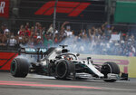 Mercedes driver Lewis Hamilton, of Britain, burns rubber as he celebrates his victory in the Formula One Mexico Grand Prix auto race at the Hermanos Rodriguez racetrack in Mexico City, Sunday, Oct. 27, 2019. (AP Photo/Eduardo Verdugo)