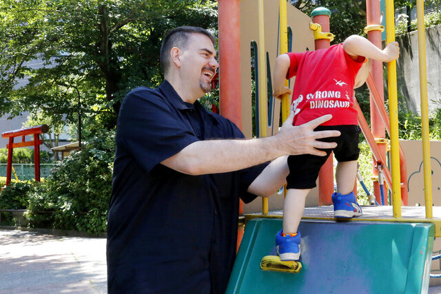 FILE - In this Monday, June 4, 2018, file photo, Glen Wood, a Canadian who has lived in Japan for 30 years, plays with his son at a Tokyo park. A Japanese court has rejected the demand by former brokerage manager Wood to get his job back after he took paternity leave at Mitsubishi UFJ Morgan Stanley. (AP Photo/Yuri Kageyama, File)