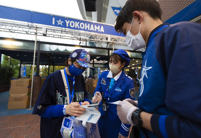A fan tries to show a mobile phone app called Cocoa created by the Japanese health ministry to help curb the coronavirus as she enters a baseball stadium before a Japanese professional baseball league game in Yokohama, south of Tokyo on Friday, Oct. 30, 2020. (AP Photo/Hiro Komae)