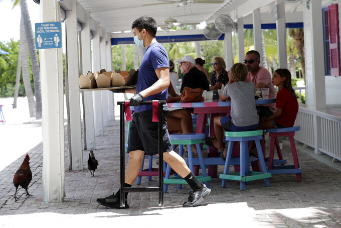 FILE - In this June 1, 2020 file photo, Charles Perez wears a protective face mask and gloves as he waits on tables at the Morada Bay Beach Cafe in Islamorada, in the Florida Keys, during the new coronavirus pandemic.  Repealing statewide mask mandates and criticizing the Biden administration's unemployment-based formula for distributing billions in federal aid has put Republican governors and their approach to handling the coronavirus pandemic back in the spotlight.  (AP Photo/Lynne Sladky)