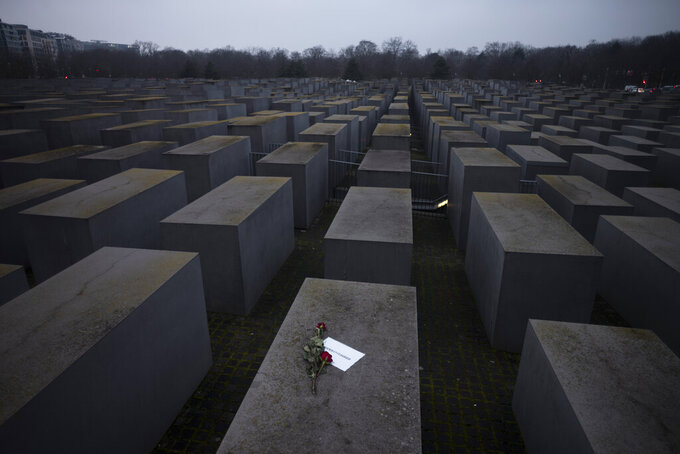"""Roses with a note saying """"#weremember"""", are placed on the Holocaust Memorial on International Holocaust Remembrance Day, in Berlin, Germany, Wednesday, Jan. 27, 2021. (AP Photo/Markus Schreiber)"""