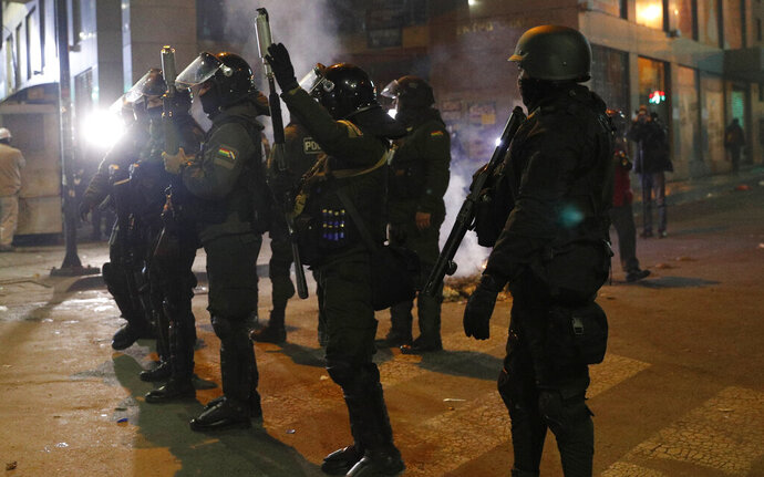 A riot police prepare to launch tear gas to disperse demonstrators who are against the reelection of President Evo Morales, in La Paz, Bolivia, Tuesday, Nov. 5, 2019. Opponents challenged an official count that showed Morales winning with 47% of the vote and a margin of just over 10 percentage points over his nearest competitor, enough to avoid the need for a runoff against a united opposition. (AP Photo/Juan Karita)