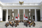 Indonesian President Joko Widodo, top row fifth from left, and his deputy Ma'ruf Amin, sixth from left, sit on the stairs of Merdeka Palace with his new cabinet ministers during the announcement of the new cabinet at in Jakarta, Indonesia, Wednesday, Oct. 23, 2019. (AP Photo/Dita Alangkara)