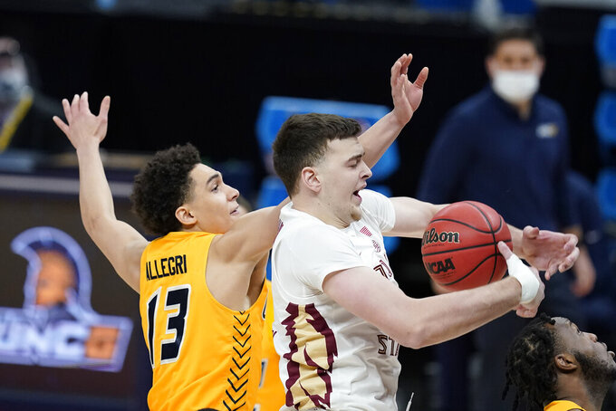 Florida State's Balsa Koprivica (5) grabs a rebound abasing UNC-Greensboro's Angelo Allegri (13) during the first half of a first-round game in the NCAA men's college basketball tournament at Banker's Life Fieldhouse, Saturday, March 20, 2021, in Indianapolis. (AP Photo/Darron Cummings)