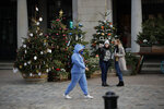 A woman wearing a face mask walks backdropped by Christmas trees in Covent Garden, during England's second coronavirus lockdown in London, Thursday, Nov. 26, 2020. As Christmas approaches, most people in England will continue to face tight restrictions on socializing and business after a nationwide lockdown ends next week, the government announced Thursday. (AP Photo/Matt Dunham)