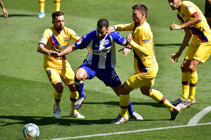 Alaves' Edgar Mendez, center, fights for the ball with Barcelona's Jordi Alba, left, and Clement Lenglet during the Spanish La Liga soccer match between Alaves and FC Barcelona, at Mendizorroza stadium, in Vitoria, northern Spain, Sunday, July 19, 2020. (AP Photo/Alvaro Barrientos)