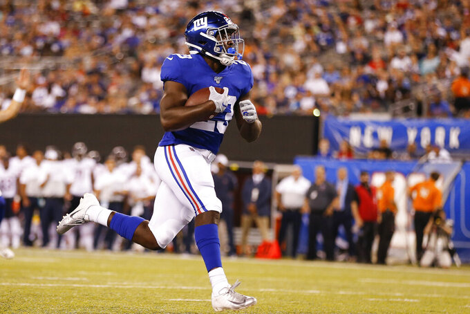 FILE - In this Aug. 16, 2019, file photo, New York Giants running back Jon Hilliman (23) scores a touchdown against the Chicago Bears during the fourth quarter of a preseason NFL football game, in East Rutherford, N.J. When Hilliman was growing up in New Jersey, he always dreamed of becoming a running back for the New York Giants. The former Boston College and Rutgers product out of St. Peter's Prep in Jersey City signed a free agent contract with the Giants last May and has a shot at fulfilling his dream this season. (AP Photo/Adam Hunger, File)