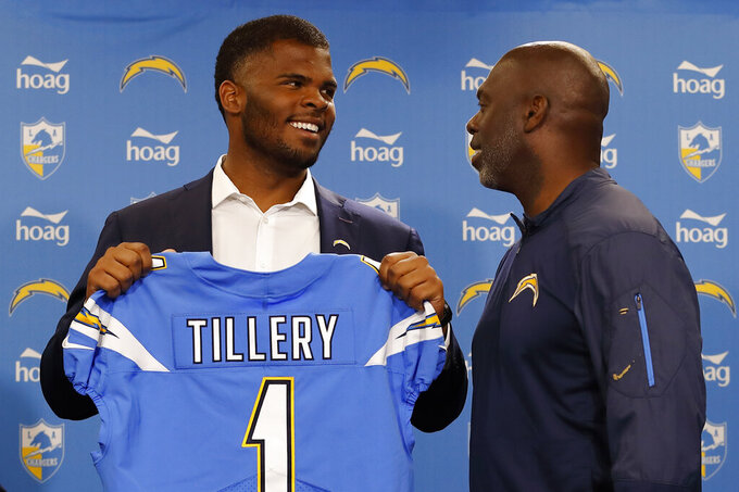 Los Angeles Chargers NFL football defensive tackle Jerry Tillery, left, poses with a jersey as he talks with head coach Anthony Lynn, right, during a news conference at Chargers headquarters Friday, April 26, 2019, in Costa Mesa, Calif. The Notre Dame defensive tackle was drafted by the Chargers in the first round Thursday. AP Photo/Gregory Bull)