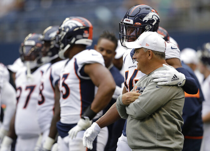 FILE - in this Aug. 8, 2019, file photo, Denver Broncos wide receiver Courtland Sutton (14) stands with coach Vic Fangio, right, before the team's NFL football preseason game against the Seattle Seahawks in Seattle. While everyone else was zigging, general manager John Elway was zagging, hiring a 61-year-old defensive minded head coach in Fangio while other teams searched for the next offensive guru. (AP Photo/Stephen Brashear, File)