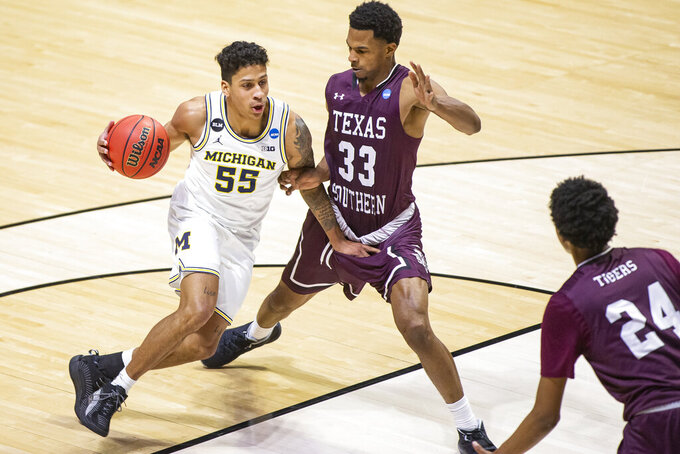 Michigan's Eli Brooks (55) drives against Texas Southern's Quinton Brigham (33) during the second half of a first-round game in the NCAA men's college basketball tournament, Saturday, March 20, 2021, at Mackey Arena in West Lafayette, Ind. (AP Photo/Robert Franklin)