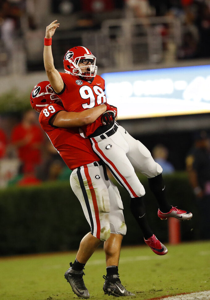 FILE - In this Oct. 6, 2018, file photo, Georgia's Rodrigo Blankenship (98) celebrates with Charlie Woerner (89) after kicking a 53-yard field goal during the second half of an NCAA college football game against Vanderbilt, in Atlanta. While Blankenship goes with a much more subdued pair of wire-rimmed specs away from the field, he definitely needs those black, goggle-like sports glasses to see what he's doing on game day. They're not some sort of fashion statement or marketing gimmick. He's unable to wear contacts, so that's really his only option. (AP Photo/John Bazemore, File)