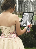 In this Saturday, May 19, 2018, photo provided by Kelly Brown, James Buchanan High School senior Kaylee Suders looks at a picture of her kissing her boyfriend Carter Brown, who died in a car wreck last month, as she was posing for photos with Carter's father Robert Brown at Green Grove Gardens in Greencastle, Pa. Robert Brown, a Pennsylvania man whose son died a month before the senior prom, escorted Suders, his late son's date to the dance Saturday. Robert Brown says he knew his son would've still wanted Suders to go to the prom. Suders says she didn't want to attend after Carter's death but changed her mind when his father asked to accompany her instead. (Kelly Brown via AP)