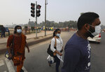 Tourists wear mask to save themselves from pollution as they cross a road amidst thick layer of smog in New Delhi, India, Tuesday, Nov. 12, 2019. A thick haze of polluted air is hanging over India's capital, with authorities trying to tackle the problem by sprinkling water to settle dust and banning some construction. The air quality index exceeded 400, about eight times the recommended maximum. (AP Photo/Manish Swarup)