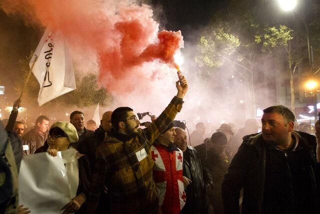 Protesters light flares as they gather at the Georgian parliament building in Tbilisi, Georgia, Monday, Nov. 25, 2019. The protests last two were sparked by last week's vote in parliament against a proposed change to the country's electoral system to ensure that all seats in the legislature are assigned by proportional representation. (AP Photo/Shakh Aivazov)