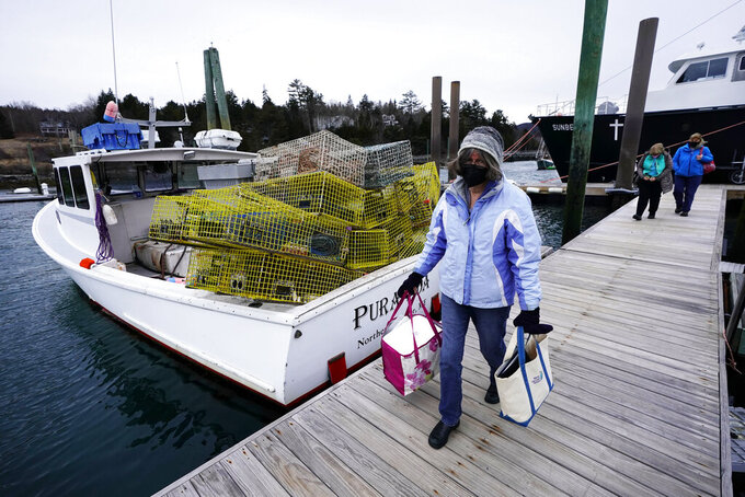 Nurse Sharon Daley carries a cooler of COVID-19 vaccinations as she and her staff begin a journey to inoculate island residents, Friday, March 19, 2021, in Northeast Harbor, Maine. (AP Photo/Robert F. Bukaty)