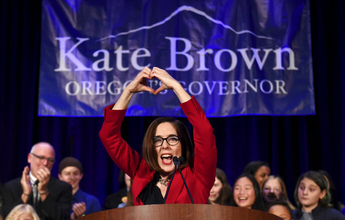 Gov. Kate Brown makes a heart-shape with her hands as she addresses the crowd after winning re-election in Portland, Ore., Tuesday, Nov. 6, 2018. (AP Photo/Steve Dykes)