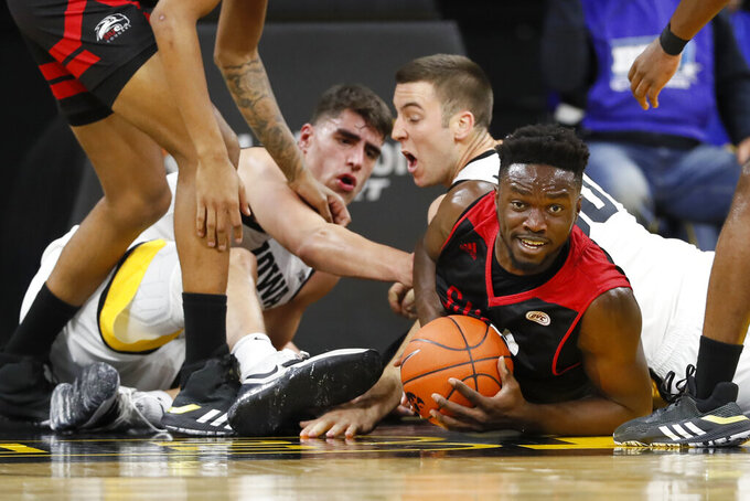 SIU-Edwardsville forward Anselm Uzuegbunem, right, fights for a loose ball with Iowa's Luka Garza, left, and Connor McCaffery during the first half of an NCAA college basketball game, Friday, Nov. 8, 2019, in Iowa City, Iowa.(AP Photo/Charlie Neibergall)