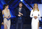 Duncan Laurence of the Netherlands is watched by presenters Lucy Ayoub, left, and Israeli mode Bar Refaeli as he holds the trophy after winning the 2019 Eurovision Song Contest grand final with the song