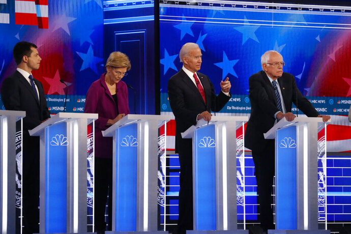 Democratic presidential candidate former Vice President Joe Biden, second from right, speaks as candidates Sen. Bernie Sanders, I-Vt.,, right, and South Bend, Ind., Mayor Pete Buttigieg, left, and Sen. Elizabeth Warren, D-Mass., second from left, watch during a Democratic presidential primary debate, Wednesday, Nov. 20, 2019, in Atlanta. (AP Photo/John Bazemore)