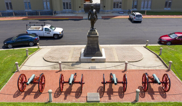 FILE - In this July 15, 2020 file photo the statue of Confederate General Stonewall Jackson stands behind canons at the entrance to the barracks at Virginia Military Institute in Lexington, Va. Virginia Military Institute's Board of Visitors voted Thursday, Oct. 29 to remove the prominent statue. (AP Photo/Steve Helber)