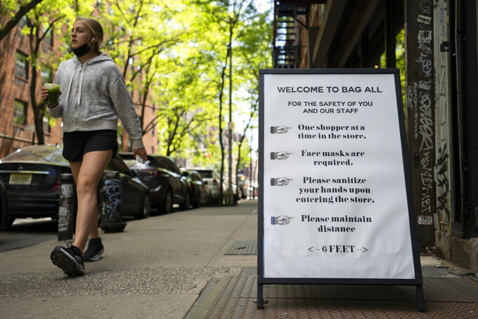A pedestrian passes a storefront sign that lists COVID-19 protective protocols required for entry in the retail shopping district of the SoHo neighborhood of the Manhattan borough of New York, Friday, May 14, 2021.  Gov. Andrew Cuomo has yet to say whether he will change his state's mask mandate in light of new federal guidance that eases rules for fully vaccinated people. (AP Photo/John Minchillo)