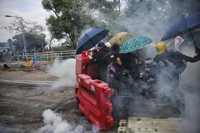 Students are surrounded by tear gas behind barricades during a clash with police at the Chinese University in Hong Kong, Tuesday, Nov. 12, 2019. Police fired tear gas at protesters who littered streets with bricks and disrupted morning commutes and lunch breaks Tuesday after an especially violent day in Hong Kong's five months of anti-government demonstrations. (Steve Leung/HK01 via AP)