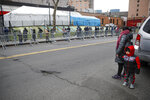 A woman and child prepare to step into a line to enter a COVID-19 testing site at Elmhurst Hospital Center, Wednesday, March 25, 2020, in New York. New York has enacted strict rules to keep residents inside as much as possible other than for essential needs such as food and medicine. (AP Photo/John Minchillo)