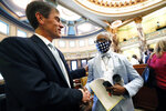 FILE - In this  June 28, 2020, file photo, Sen. Briggs Hopson, R-Vicksburg, left, is congratulated by Sen. Hillman Frazier, D-Jackson after the Senate voted to change the Mississippi state flag at the Capitol in Jackson, Miss. Hopson presented the bill to the body. Both chambers of the Mississippi Legislature passed the bill to take down the state flag, which contains the Confederate battle emblem. (AP Photo/Rogelio V. Solis, File)