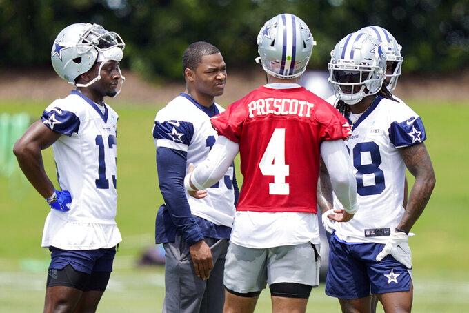 Dallas Cowboys quarterback Dak Prescott (4) speaks with wide receivers Michael Gallup (13), Amari Cooper (19) and CeeDee Lamb (88) during an NFL football team practice Tuesday, June 8, 2021, in Frisco, Texas. (AP Photo/LM Otero)