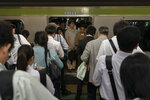 Commuters wait in line for the next train to arrive in front of a packed train during morning rush hours at Shinjuku Station in Tokyo, May 31, 2019. The station holds the Guinness World Record for being the world's busiest transport hub. An average of 3.64 million passengers pass through the station daily, according to the Guinness Worlds Records. (AP Photo/Jae C. Hong)