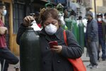 A woman wearing a mask to prevent the spread of the new coronavirus stands in line to refill her empty oxygen cylinder in Callao, Peru, Wednesday 3, 2020. Long neglected hospitals in Peru and other parts of Latin America are reporting shortages of Oxygen as they confront the COVID-19 pandemic. (AP Photo/Martin Mejia)