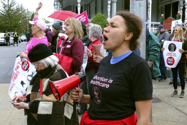 FILE - In this May 23, 2019, file photo, Tammy Brown, of Cranston, R.I, leads the crowd in chants outside a fundraiser for the Rhode Island Senate Democrats political action committee in Providence, R.I. Gov. Gina Raimondo signed legislation passed by the General Assembly in June to preserve federal abortion protections in state law. (AP Photo/Jennifer McDermott, File)