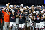 The Illinois team celebrates with the trophy after defeating Ohio State in an NCAA college basketball championship game at the Big Ten Conference tournament, Sunday, March 14, 2021, in Indianapolis. Illinois won in overtime. (AP Photo/Darron Cummings)